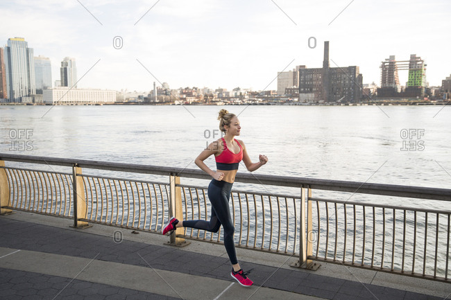 Female athlete running on promenade by East River
