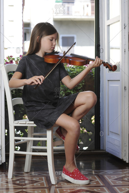 Girl playing violin while siting on chair at home