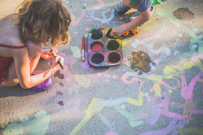 High angle view of playful siblings painting on road