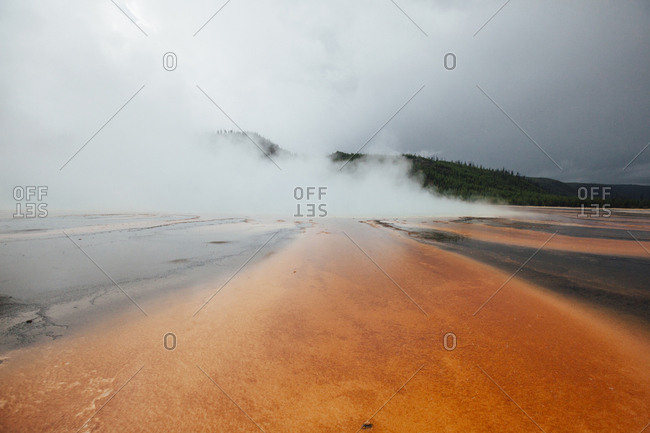 Grand prismatic spring against cloudy sky