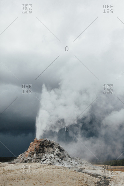 Scenic view of geezer against cloudy sky at Yellowstone national park