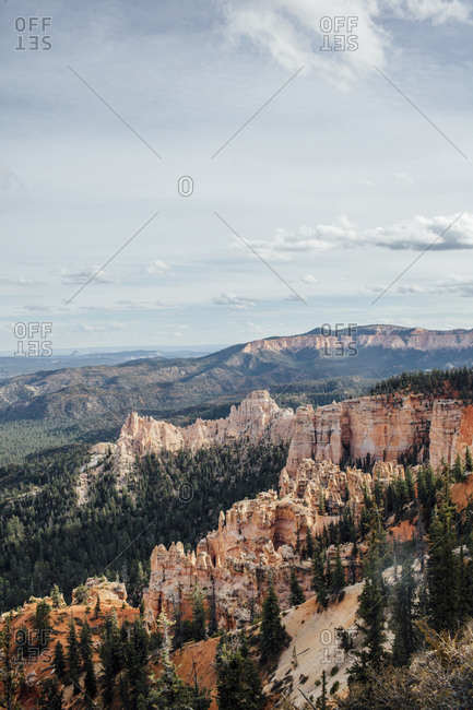 Scenic view of trees and rock formations against cloudy sky