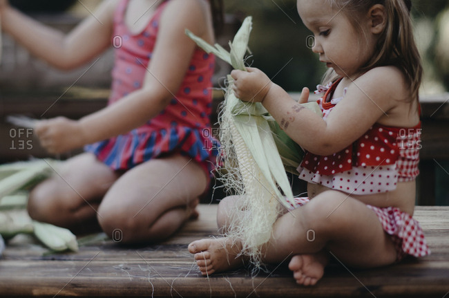 Sisters removing corn husk while sitting on bench