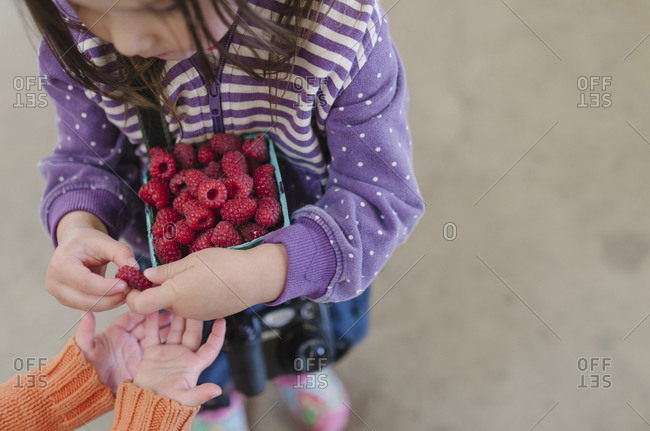 Overhead view of girl giving raspberry to sister