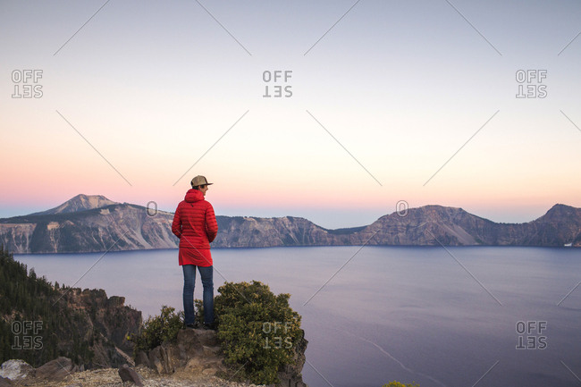 A young woman in a red coat stands on a rock outcrop overlooking a vas