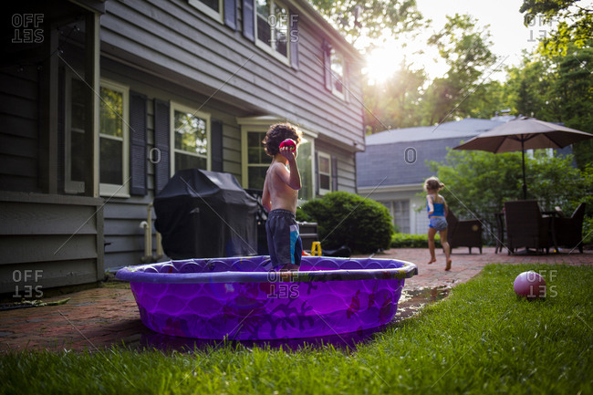 Girl running while brother standing in wading pool at backyard