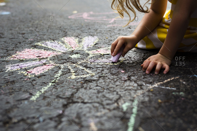 Cropped image of girl drawing flower on road