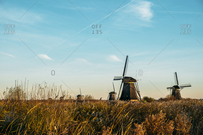 Traditional windmills on field against sky