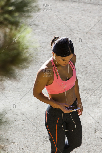 High angle view of athlete listening music while standing on footpath
