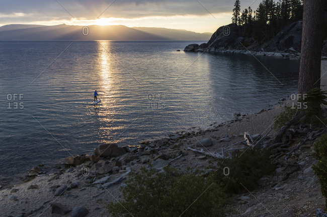 Distant view of man paddle boarding in lake during sunset