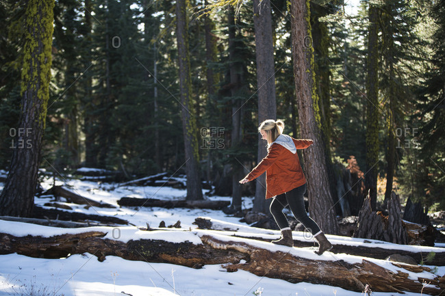 Side view of woman with arms outstretched walking on fallen tree trunk in forest during winter