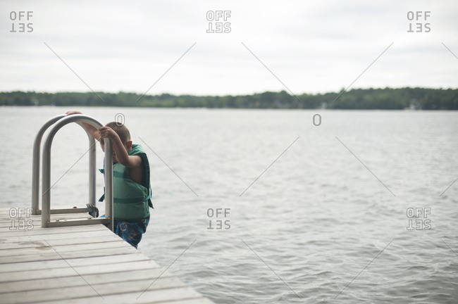 Boy climbing ladder of jetty against sky