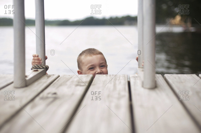 Portrait of happy boy climbing ladder of jetty against sky