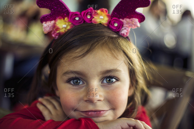 Close-up portrait of smiling girl wearing antlers while resting on table at cafe