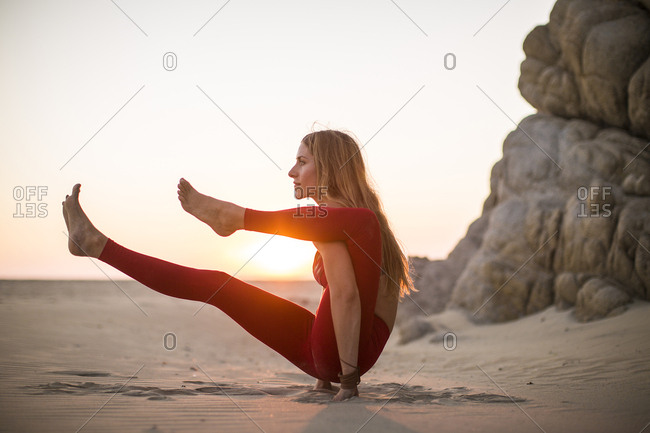 Side view of woman practicing yoga at beach against clear sky during sunset
