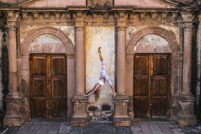 Woman practicing yoga on architectural columns of old building