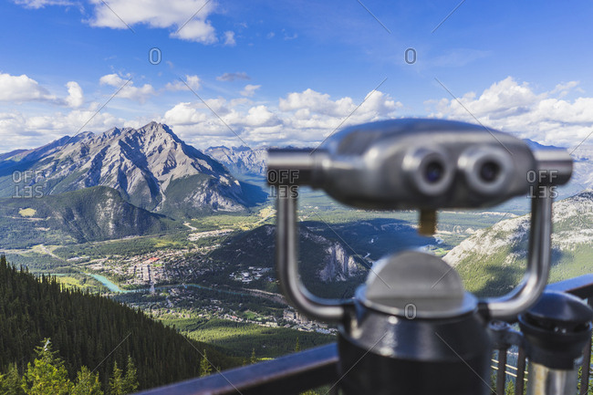 Coin-operated binoculars at observation point against mountains on sunny day