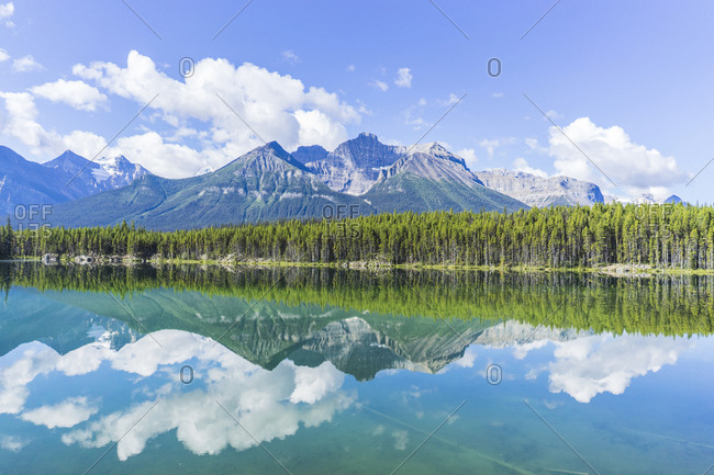 Lake by trees against mountains in sunny day