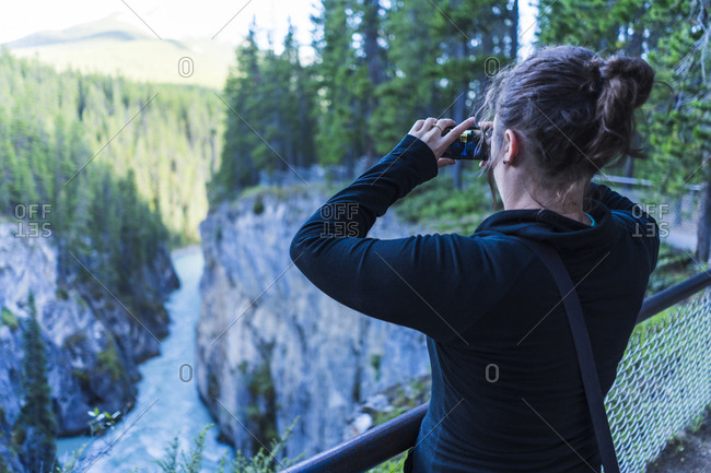 Rear view of woman photographing trees while standing at observation point
