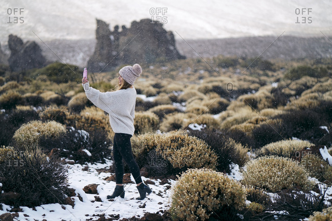 Side view of woman taking selfie while standing on field during winter