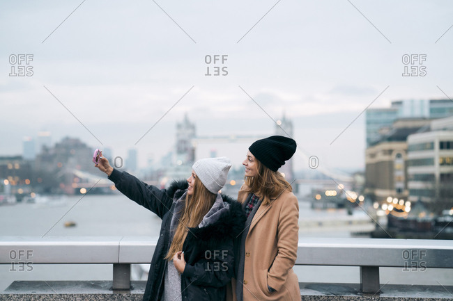 Friends taking selfie while standing against river in city against tower bridge