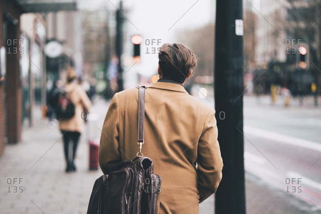 Rear view of man with shoulder bag walking on footpath in city