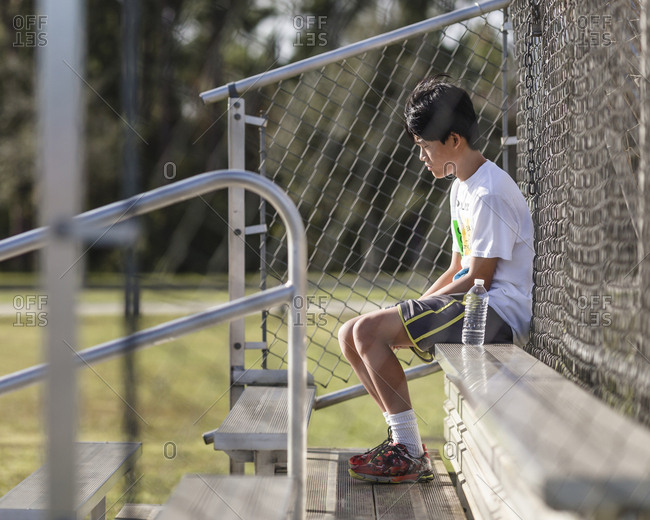 Thoughtful teenage boy sitting on bench against chain-link fence at playing field