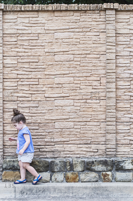Side view of girl walking on footpath against wall
