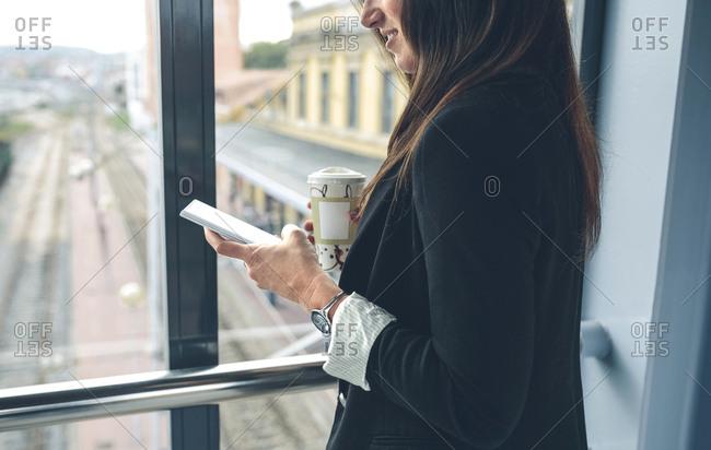 Side view of woman using mobile phone on footbridge