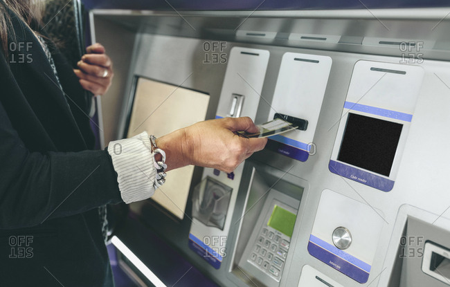 Midsection of woman inserting card in ATM machine