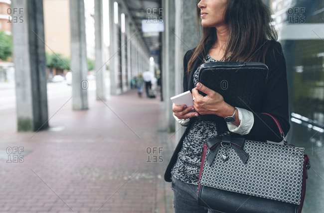 Midsection of woman holding mobile phone with purse standing by window