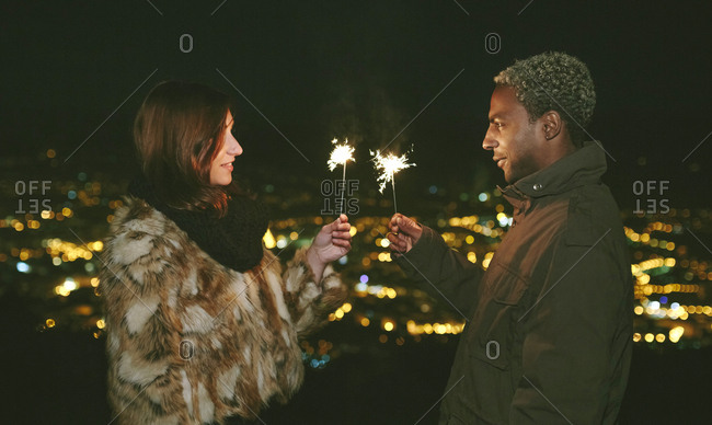 Young couple standing face to face while holding sparklers during night