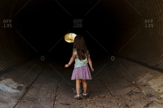 Rear view of girl walking in tunnel
