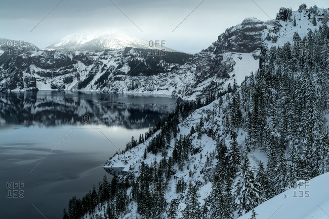 Scenic view of Crater Lake by snow covered mountains