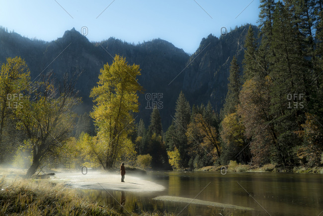 Female hiker standing by river against mountains at Yosemite National Park