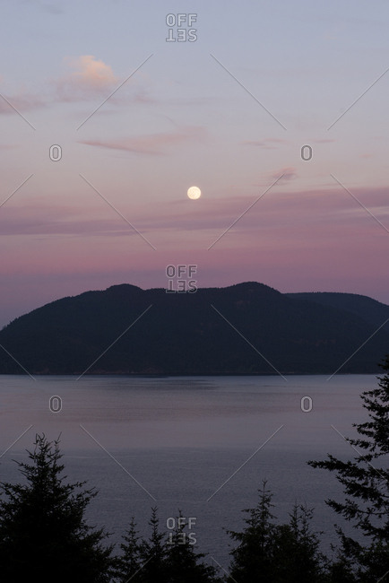 Scenic view of sea against silhouette mountain at dusk
