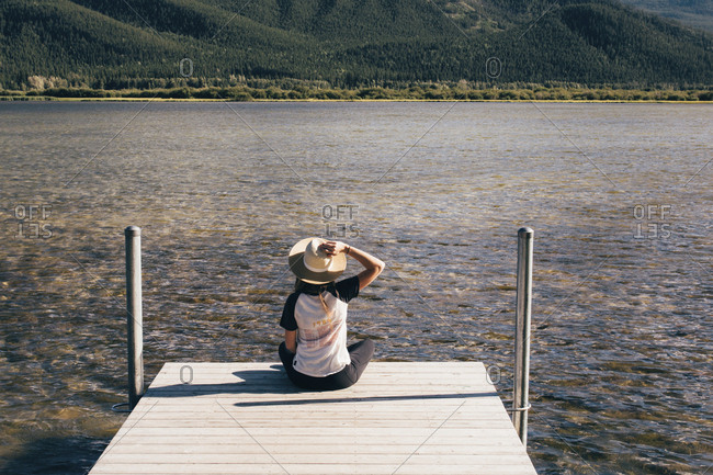 Rear view of woman sitting on jetty by lake