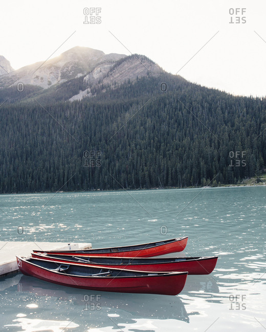 Canoe moored in lake by mountain against clear sky