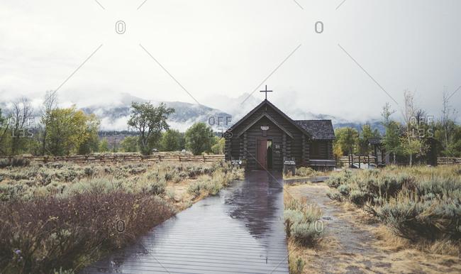 USA, Wyoming, Grand Teton National Park - September 14, 2016: Wet boardwalk leading towards church at Grand Teton National Park