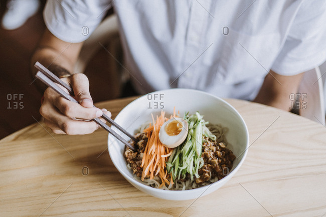 Man using chopsticks to eat a Taiwanese noodle bowl