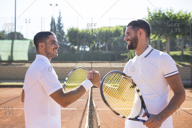 Side view of two tennis players with rackets shaking hands and smiling before tennis match