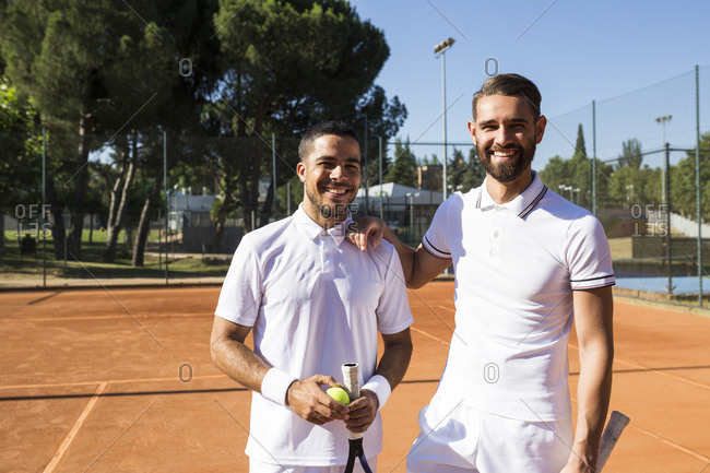 Two men in white sportswear holding rackets and smiling while standing on tennis court