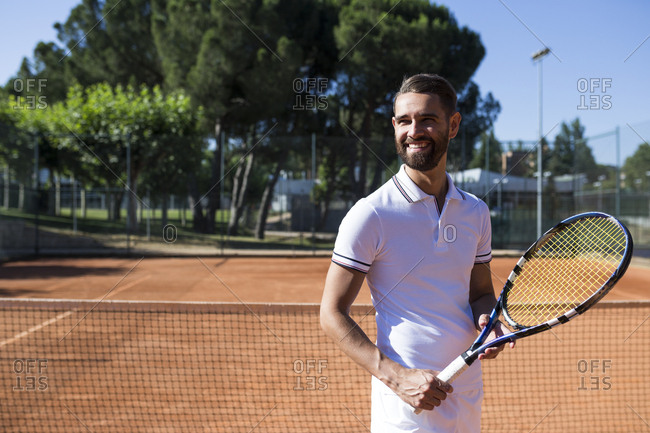 Attractive bearded man in tennis wear holding racket and looking away