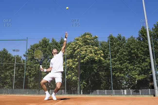 Tennis player serving a tennis ball during a tennis match