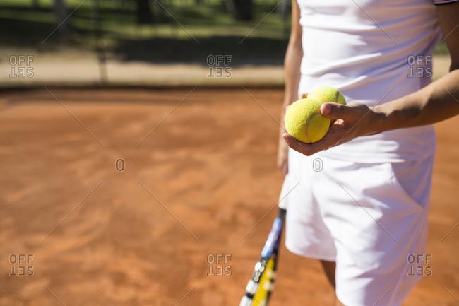 Man holding tennis balls during tennis match