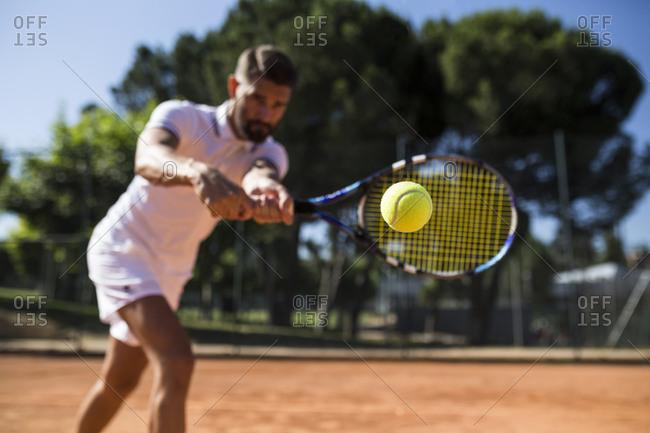 Tennis player during a tennis match- focus on tennis ball