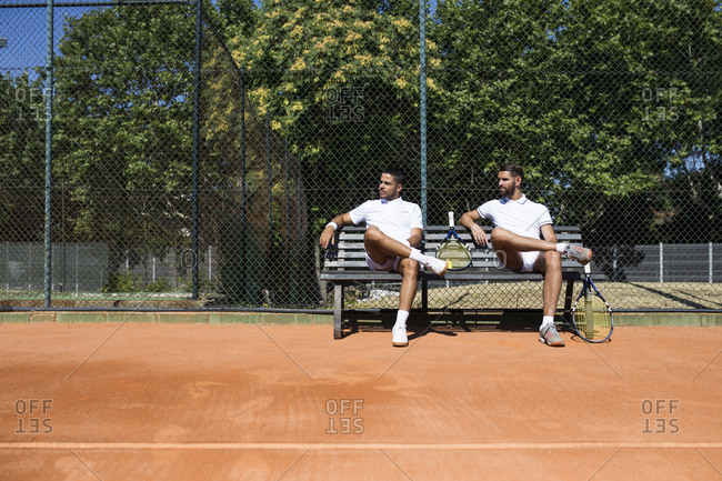 Tennis players sitting on a bench during break and looking sideways