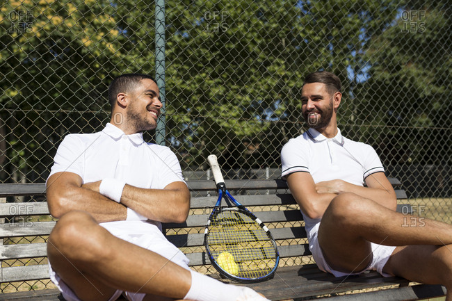 Tennis players sitting on a bench and talking during break