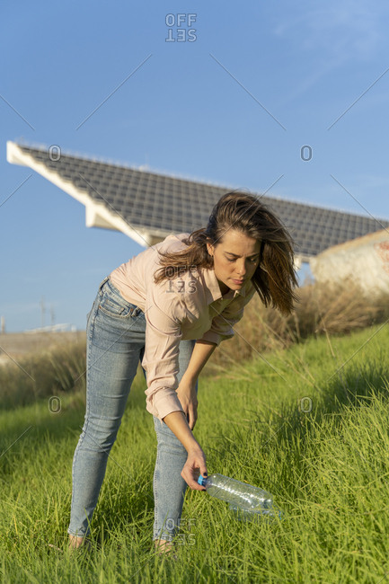 Woman on a meadow picking up empty plastic bottle
