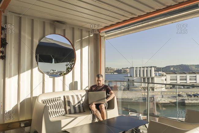 Man using laptop on a sunny terrace- Lisbon- Portugal